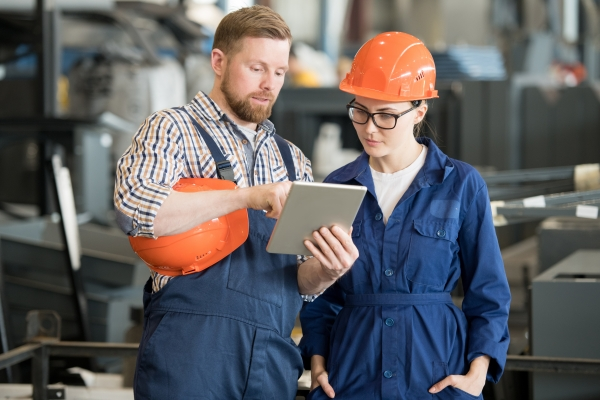 Young female engineer in uniform and helmet looking at tablet display while listening to colleague explanation of data